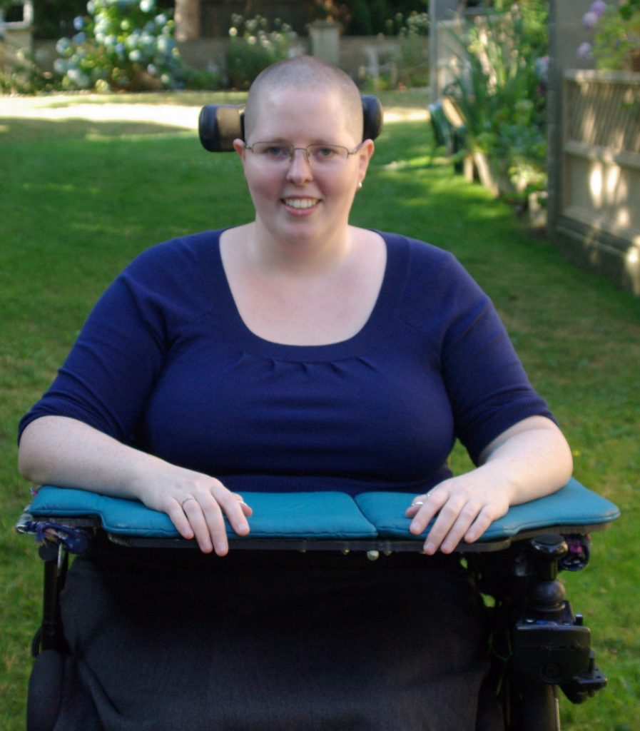 Photo of Heather in wheelchair with arms resting on a tray.