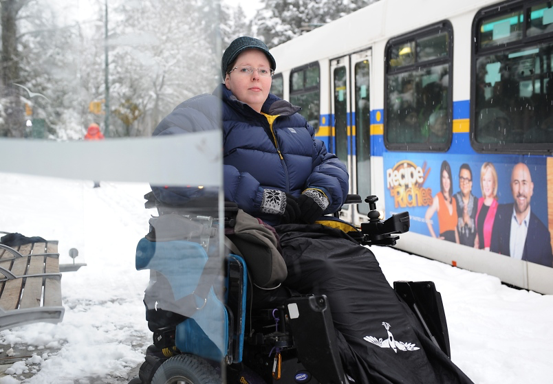 Heather McCain is bundled up in a warm jacket is sitting in a power wheelchair, slightly obscured by the glass of the bus stop. Beside them is a TransLink bus.